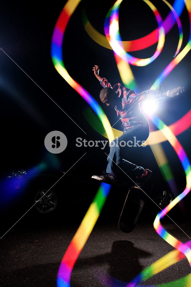 A young skateboarder doing jumping and kick flip tricks under dramatic rim lighting with lens flare and colorful rainbow light trails.