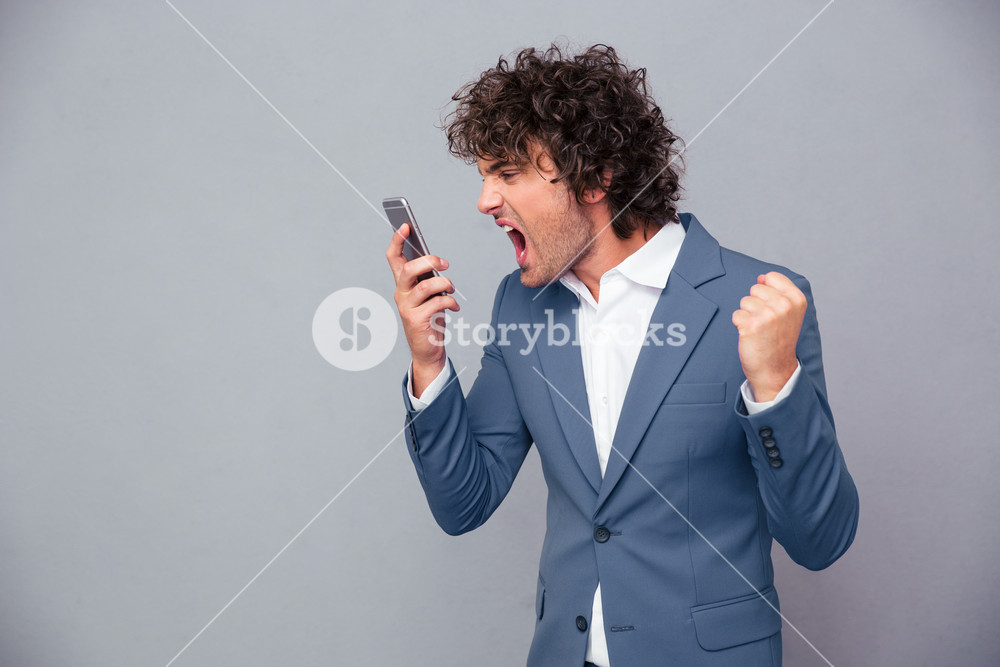 Angry businessman shouting on smartphone