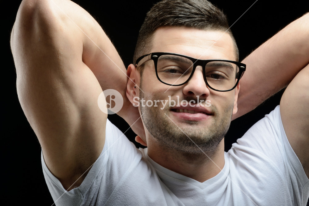 Bearded male model with glasses smiling with his hands behind his head