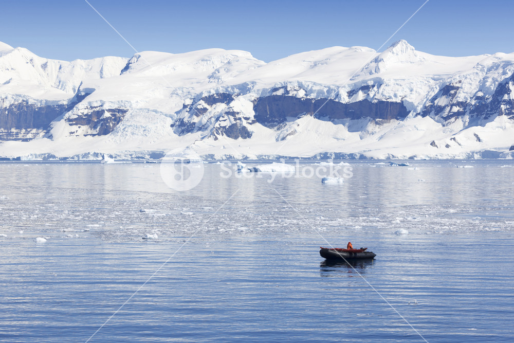 Boater traveling past a snowy coast