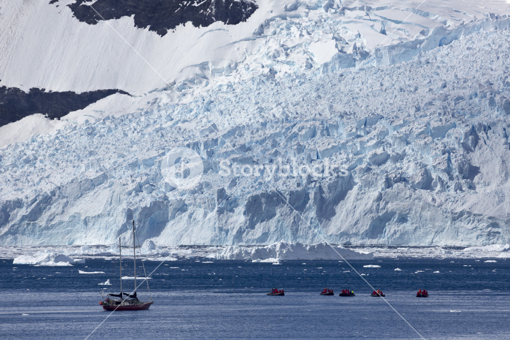 Boats traveling past a sunlit, snowy coast