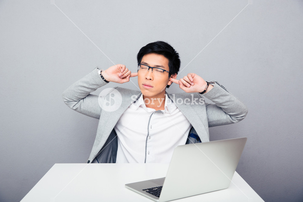 Businessman sitting at the table and covering his ears