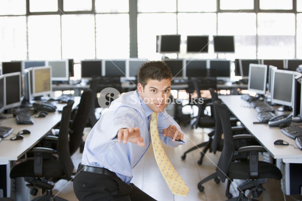 Businessman standing in karate stance in computer room