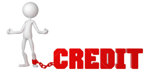 Businessman With A Foot Chained To A Credit Sign