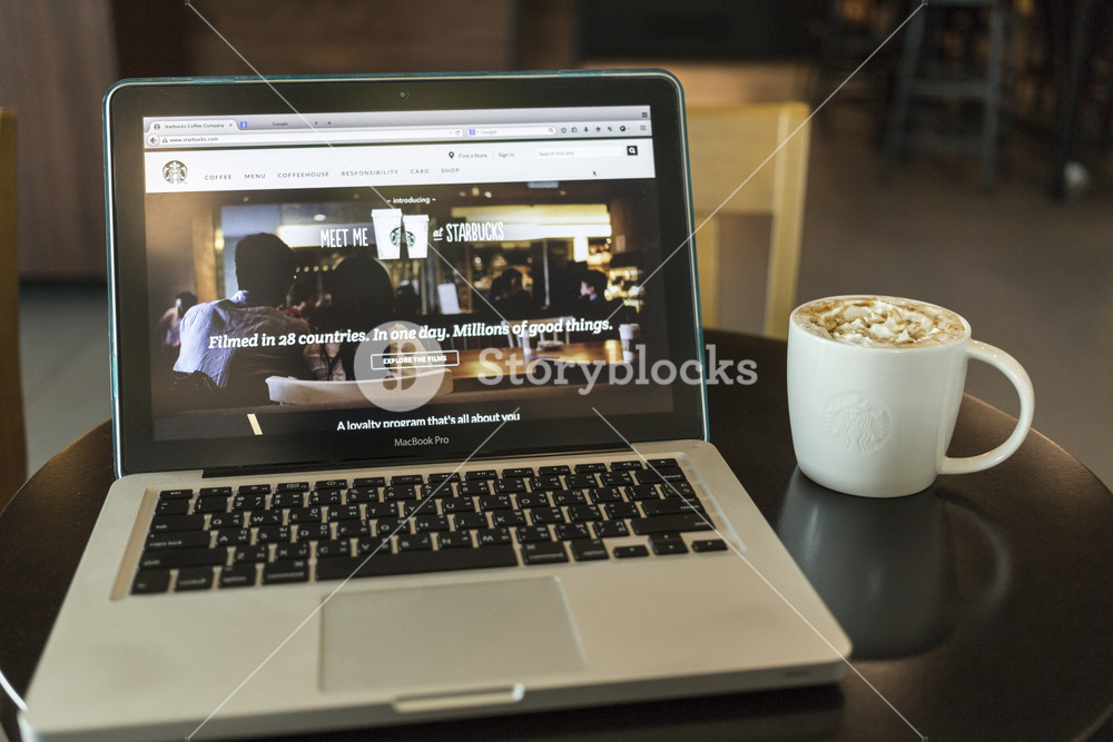 CHIANG MAI, THAILAND - OCTOBER 02, 2014: Starbucks coffee caramel latte and Apple laptop open Starbucks website on monitor.