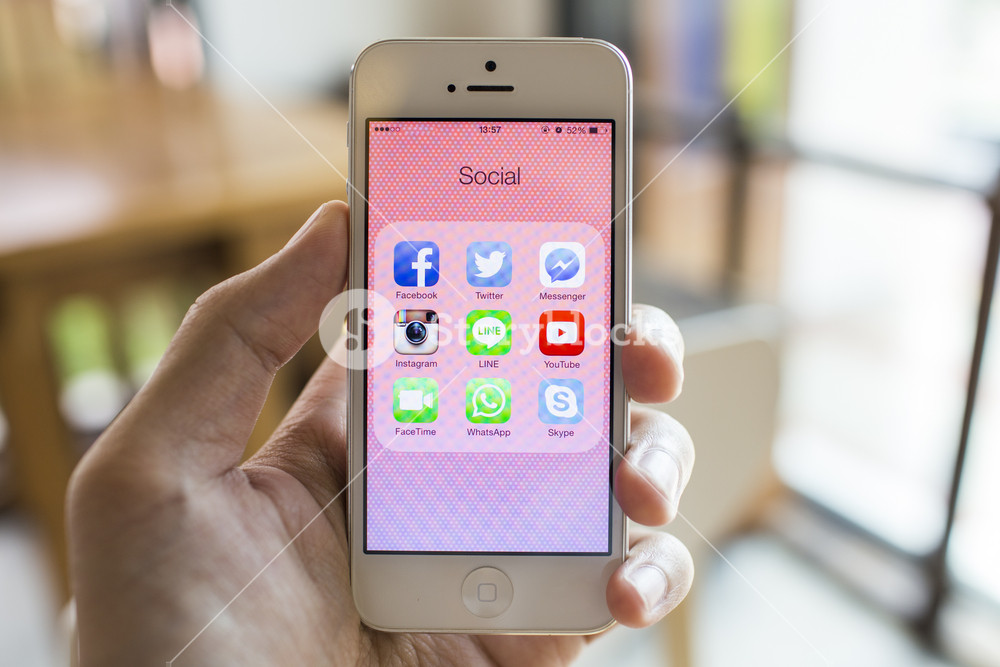 CHIANG MAI, THAILAND - SEPTEMBER 07, 2014: All of popular social media icons on smartphone device screen with hand holding on Apple iPhone 5.
