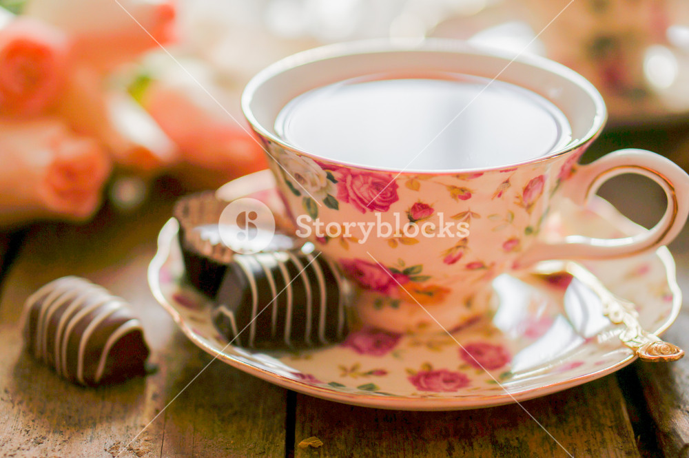Close Up Of A Cup Of Tea With Roses And Chocolate Candies On Wooden Table