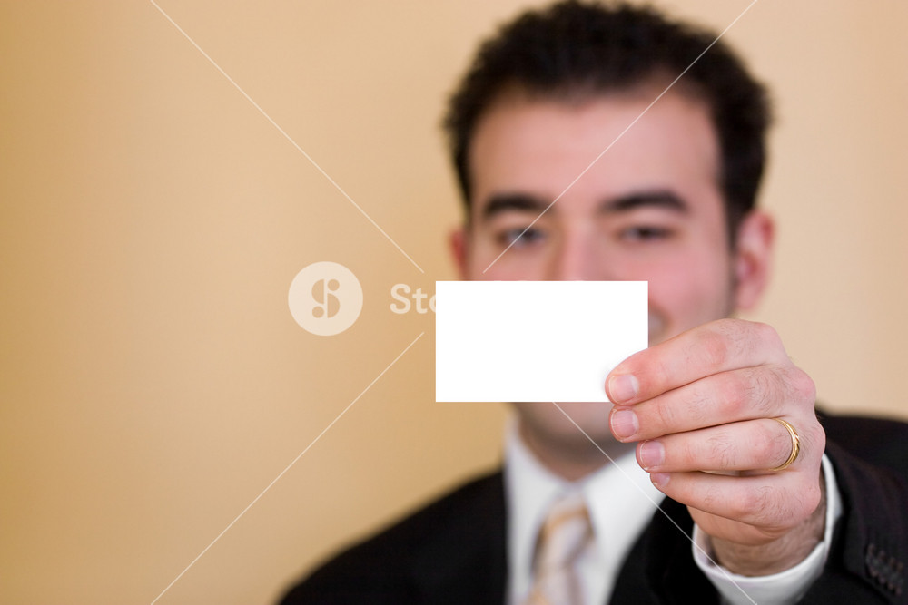 Close up of a man holding a business card up.  Plenty of copyspace for your logo or design.  Shallow depth of field.