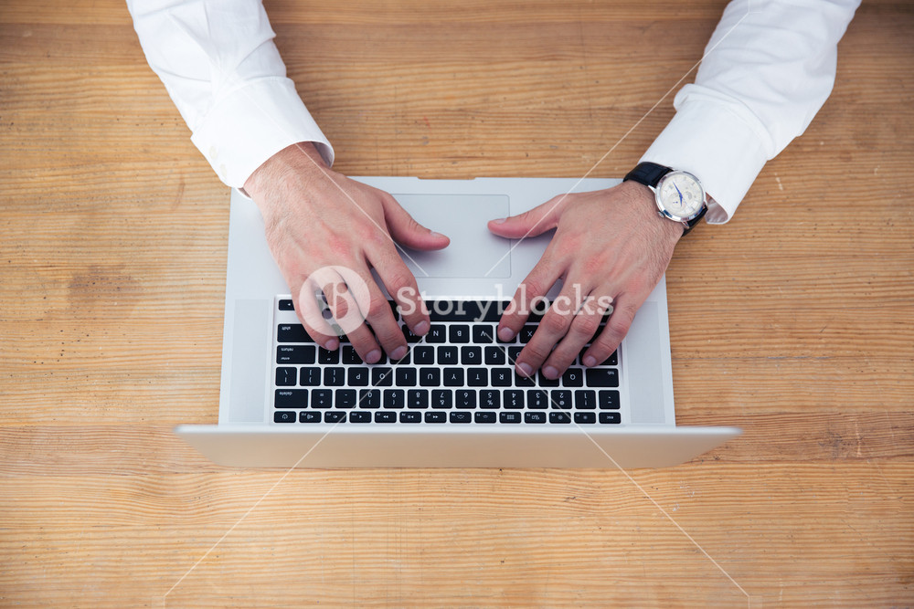 Closeup image of a businessman hands using laptop