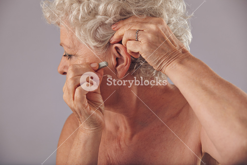 Closeup of a mature woman inserting a hearing aid in her ear. Focus on the hearing aid. Old woman wearing a hearing aid on grey background.