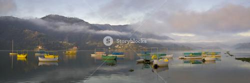 Colorful boats on a foggy lake