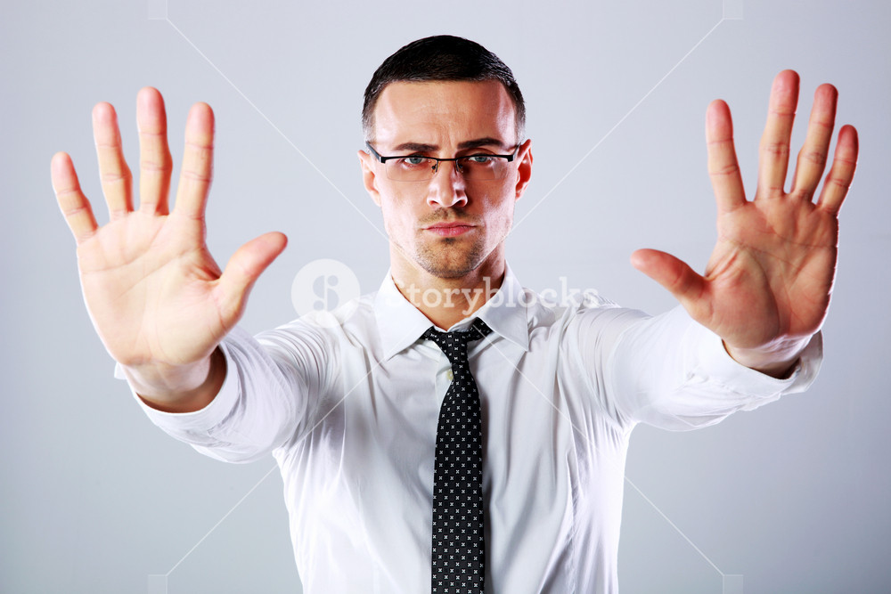Confident businessman gesturing stop sign with both hands on gray background