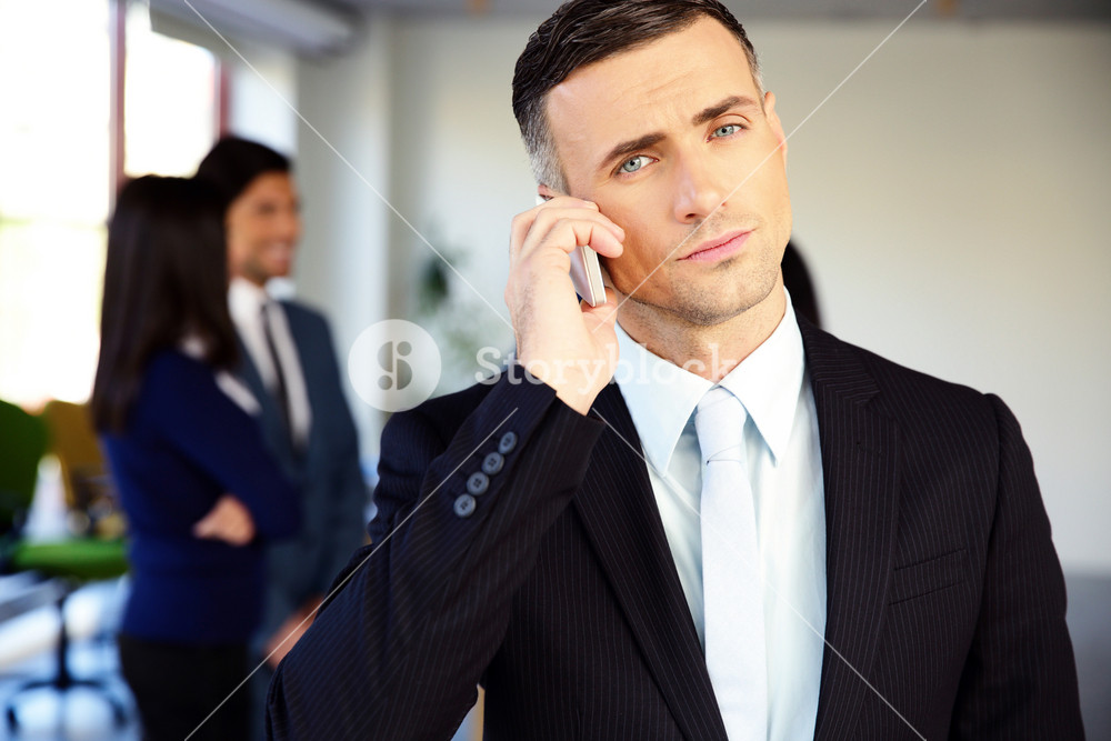 Confident businessman talking on the phone in office