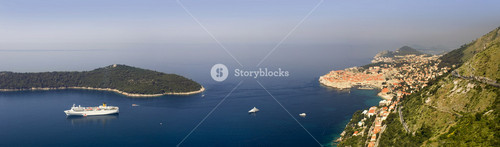 Cruise ship traveling past a coastal village and island