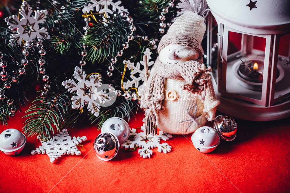 Cute little adorable snowman is standing near the white fairy lantern and decorated fir tree branch behind it. Christmas card with copy space for your text.