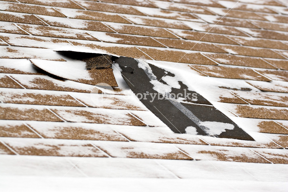 Damaged roof shingles blown off a home from a windy winter storm with strong winds.