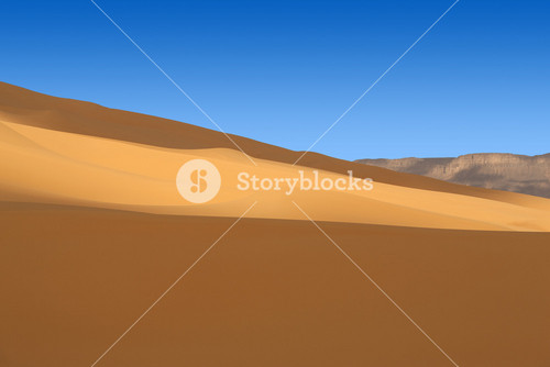 Desert sand dunes under a clear blue sky
