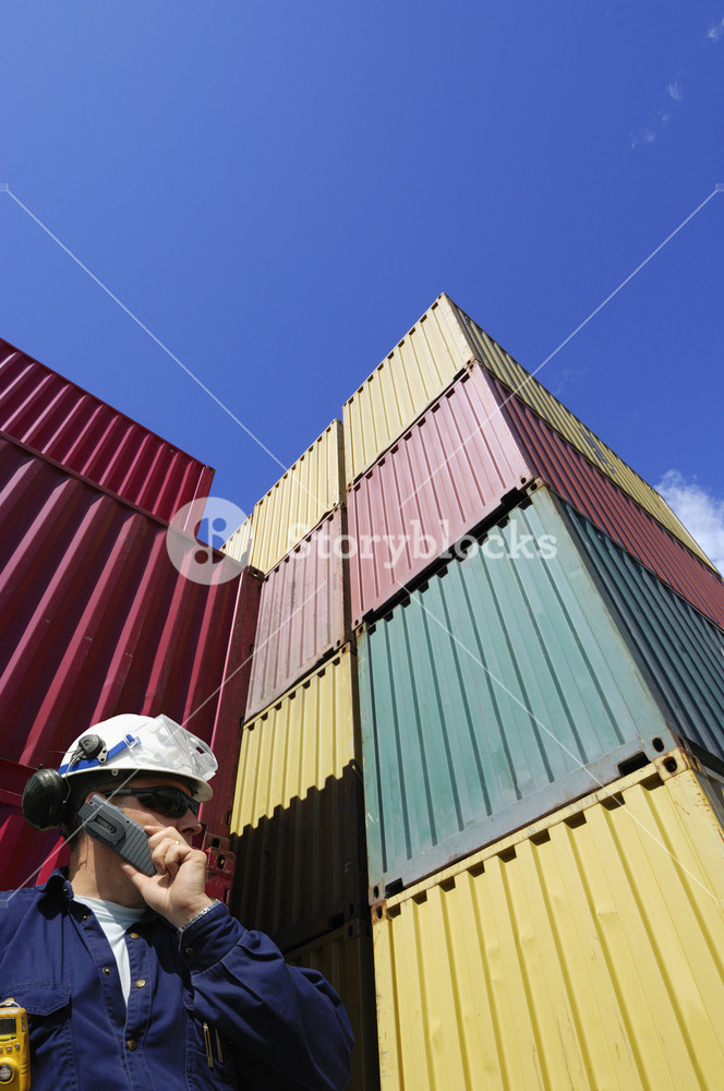 dock worker talking in phone, large stacks of shipping containers in background