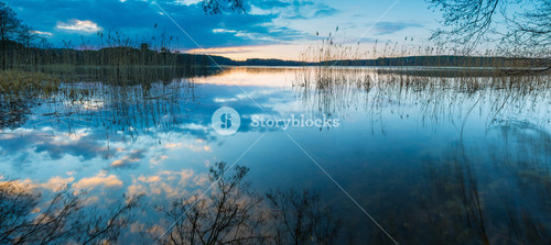 Evening lake landscape with sky reflected in water. Beautiful polish lake in Mazury lake district near Olsztyn.