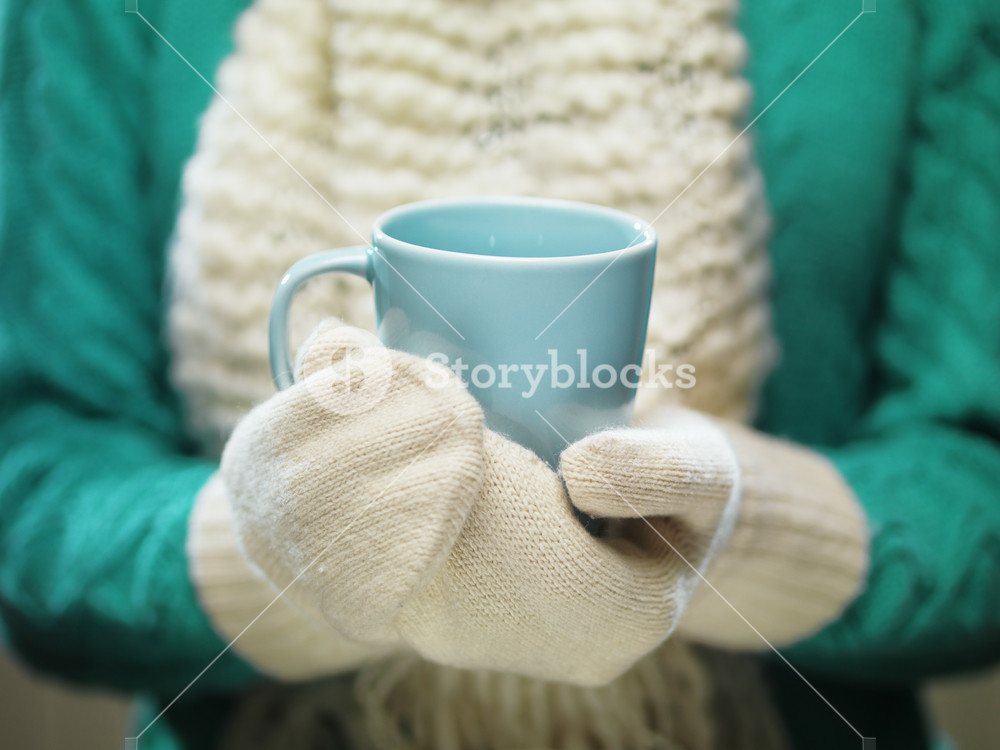 Female hands holding hot mug close up. Woman hands in white woolen mittens holding a cozy cup with hot cocoa