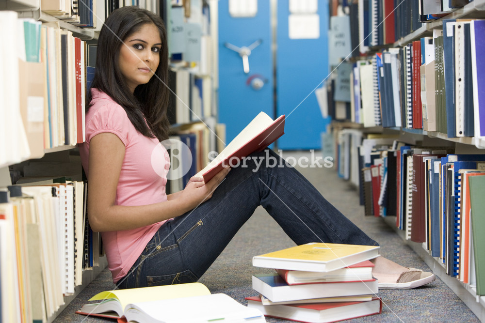 Female student sitting on library floor surrounded by books