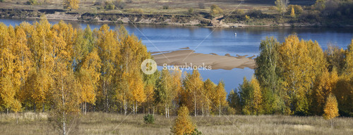 Golden trees and farmland along a riverbank
