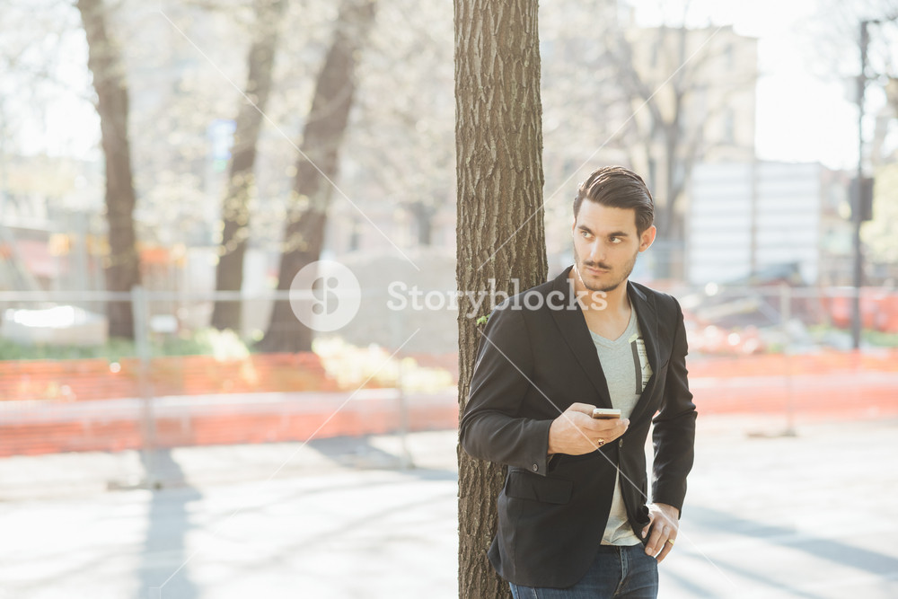 A young handsome italian boy leaning on a tree using a smartphone connected online- technology, social network concept