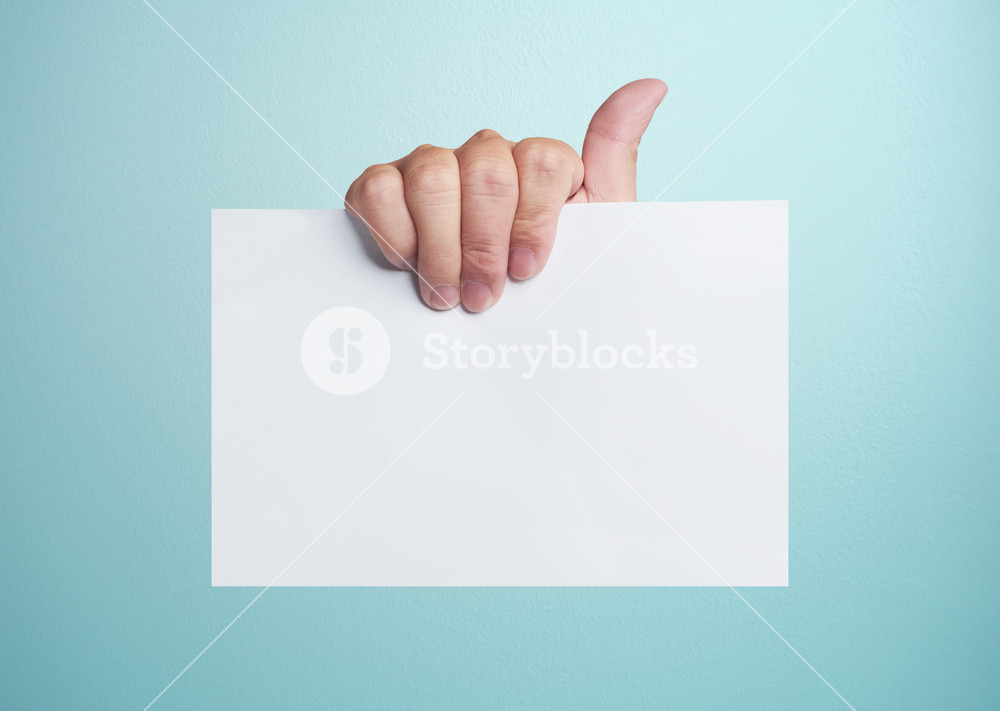 Advertising: Hand holding white empty paper .