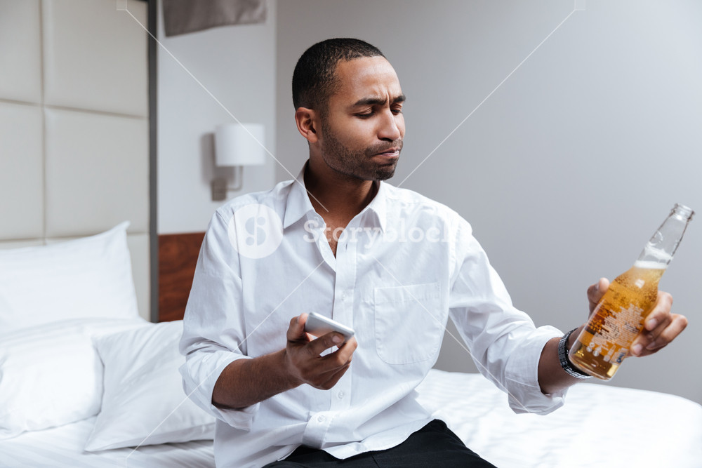 African man in shirt drinking beer in hotel room and holding phone