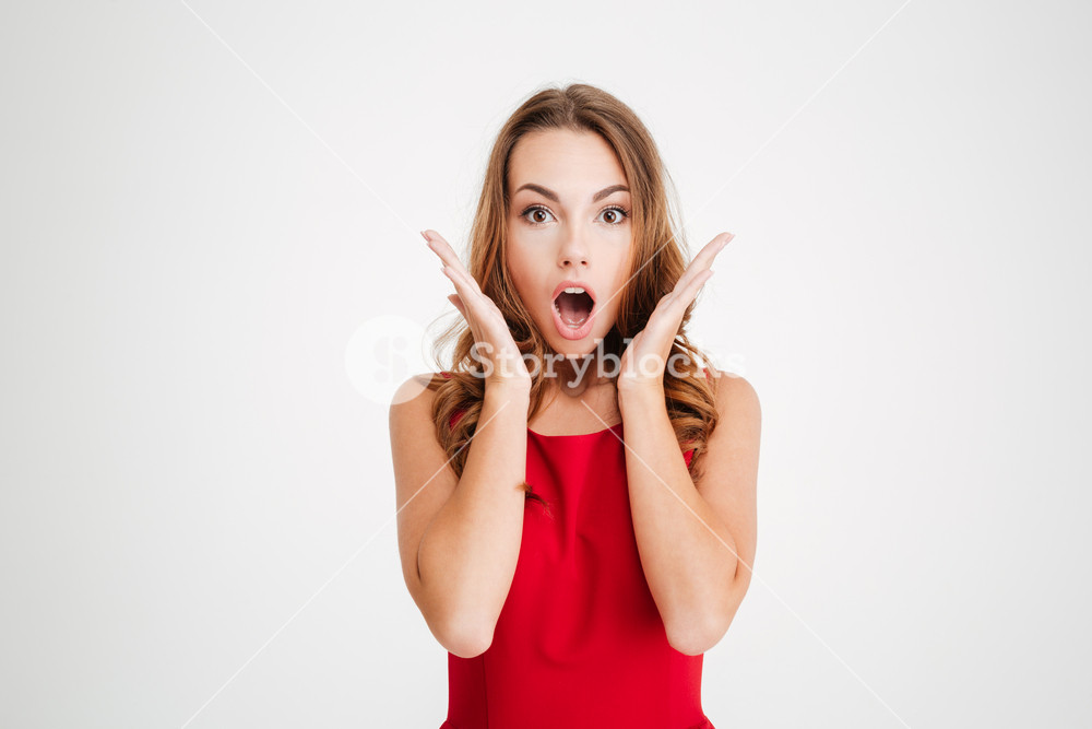 Amazed pretty young woman with opened mouth over white background