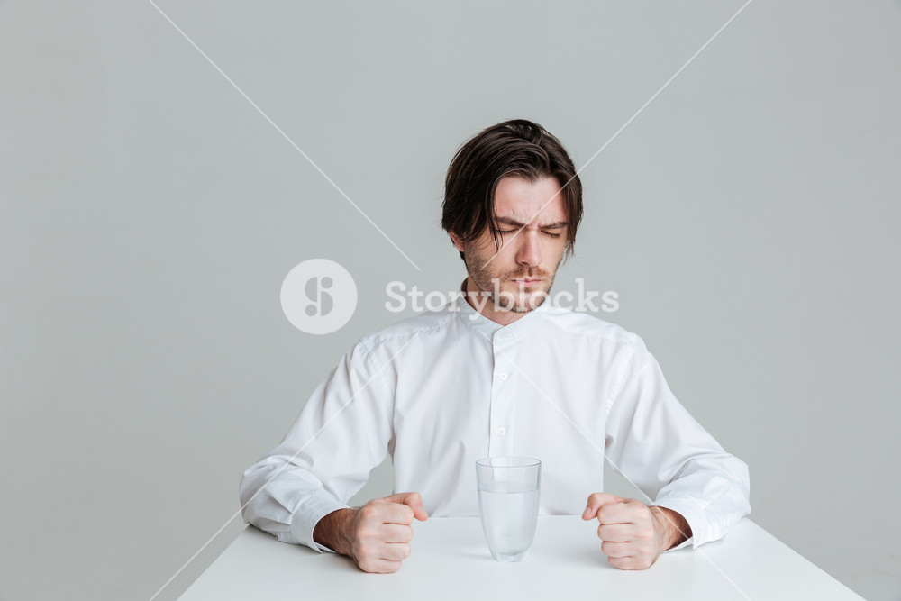 Angry frustrated brunette man sitting at the table with water glass isolated on the gray background