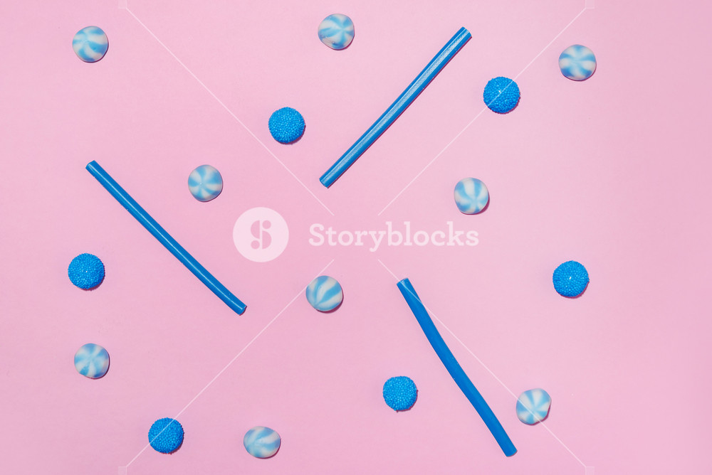 Assortment of a blue sugar jelly candies and lollies isolated on pink background