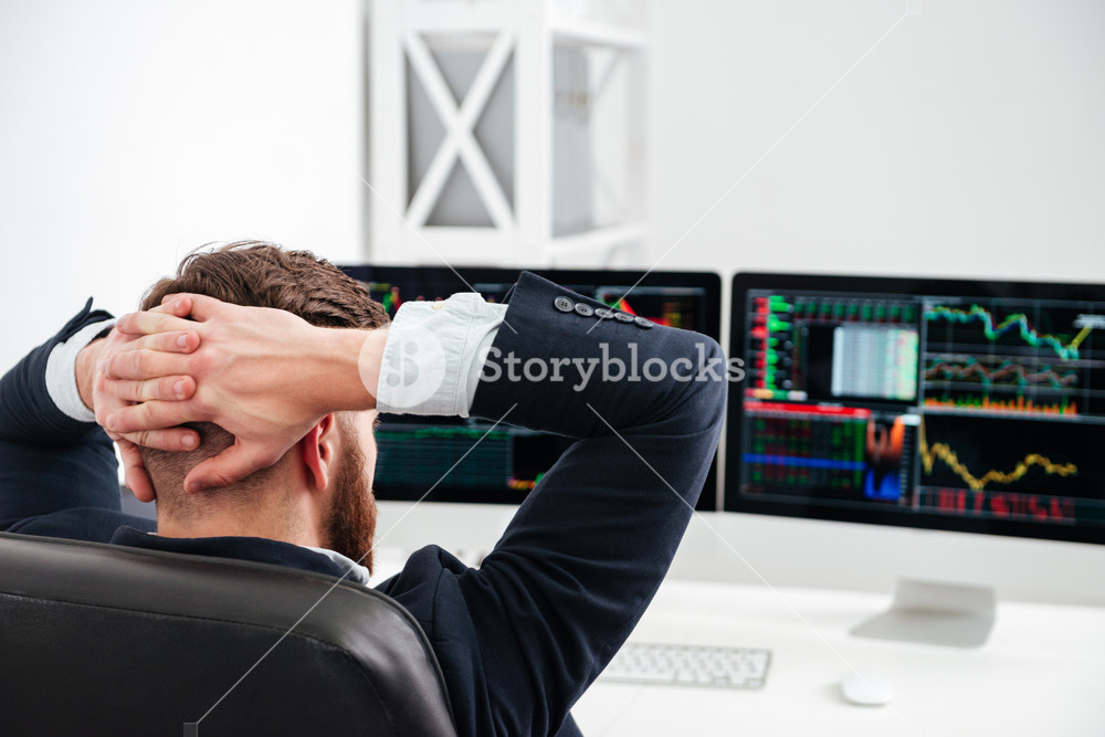 Back view of relaxed businessman sitting at workplace with hands behind head