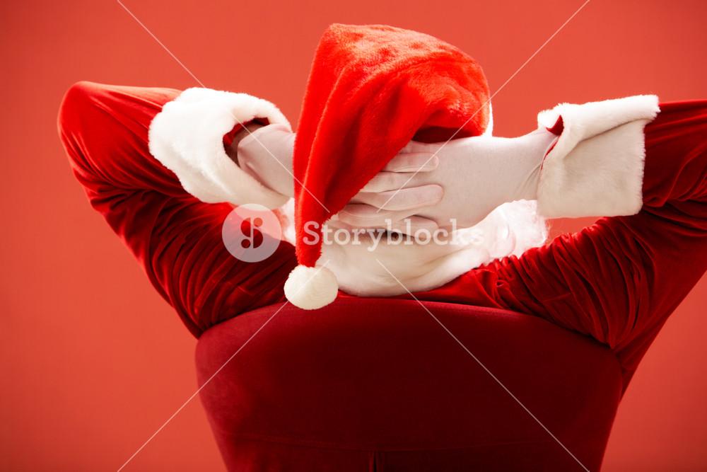 Back view of Santa Claus keeping his hands behind head