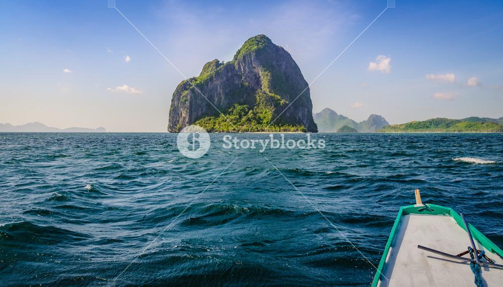 Banca Boat approaching Huge Rocky Island on Windy Day, El, Nido, Palawan, Philippines