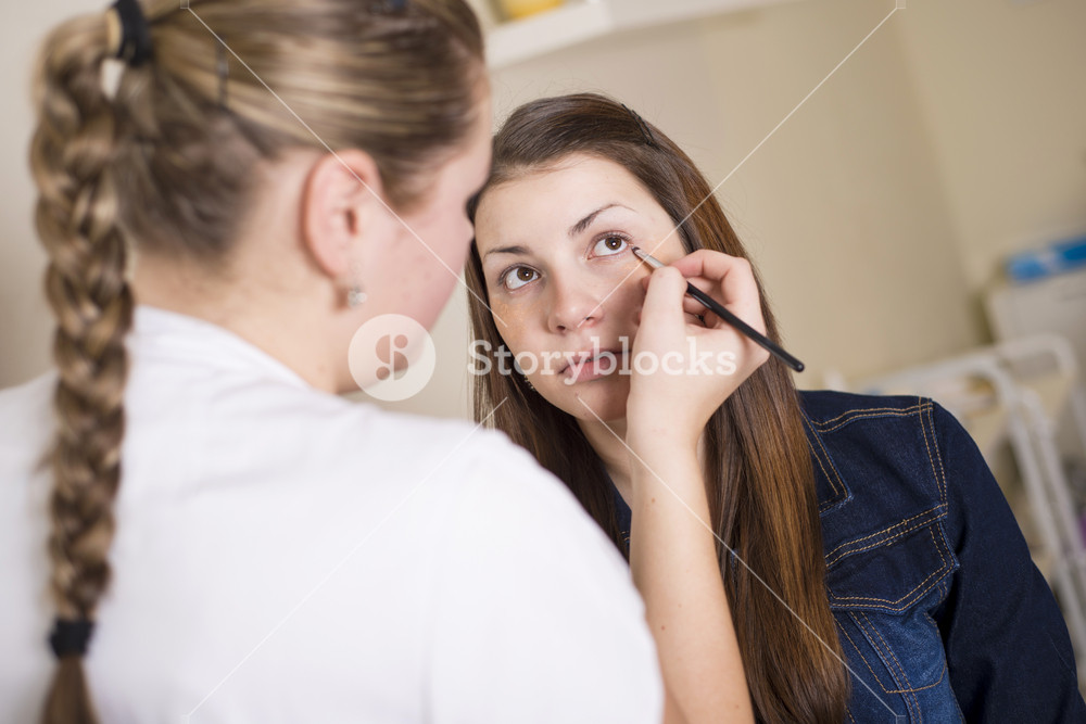 Beautician doing professional make up of young woman