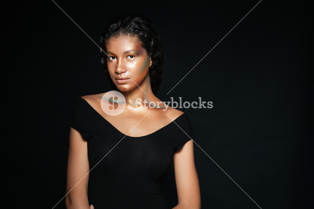 Beautiful african american young woman with fashion makeup standing and looking at camera over black background