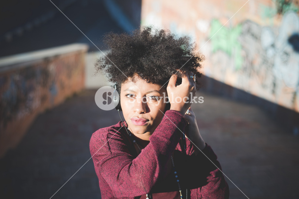 beautiful black curly hair african woman listening to music with headphones in town