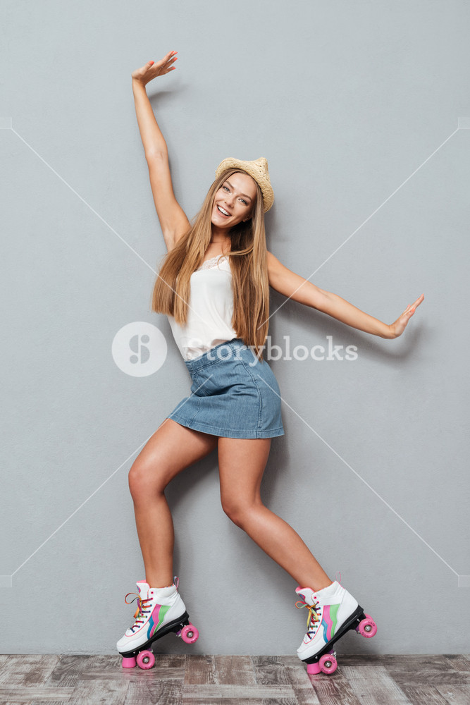 Beautiful cheerful smiling girl in hat and roller skates posing and looking at camera isolated on a gray background