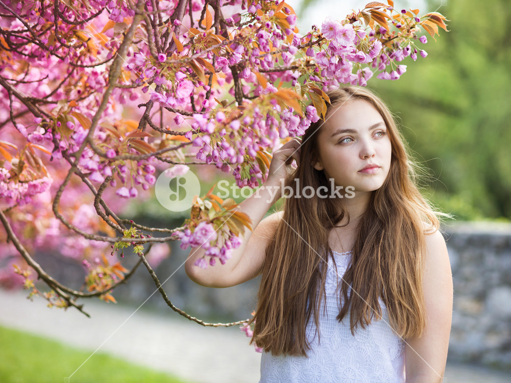Young Woman Walking In The Spring Garden Stock Photo