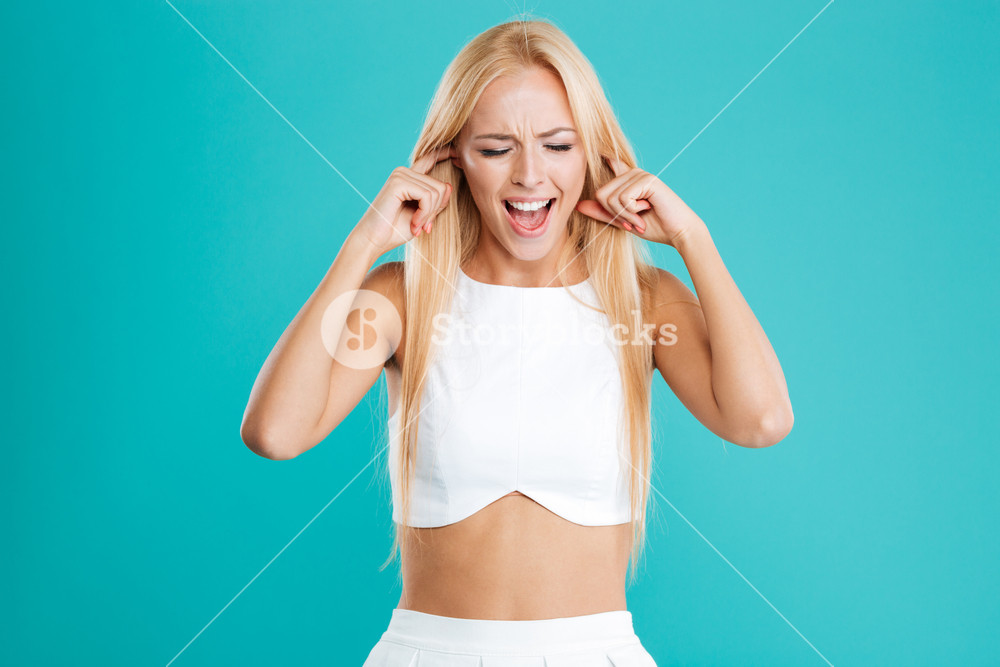 Beautiful young blonde woman covering her ears with fingers isolated on the blue background