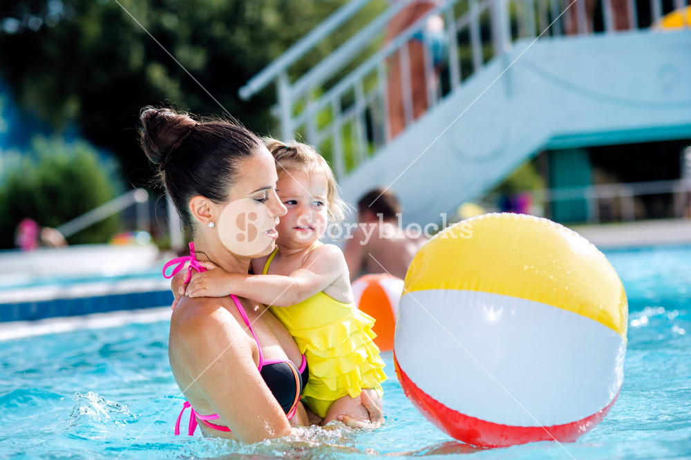 Beautiful young mother with her daughter holding colorful beach ball in swimming pool in aqua park. Summer heat and water.