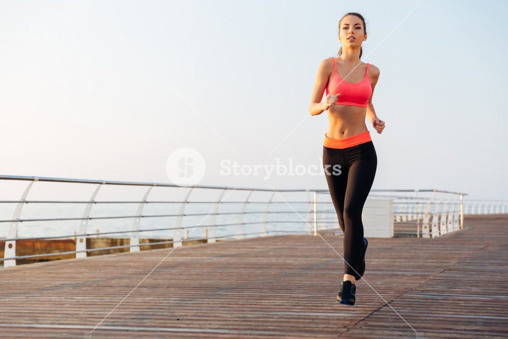 Beautiful young sportswoman training and running on pier in the morning