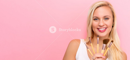Beautiful young woman holding makeup brushes on a pink background