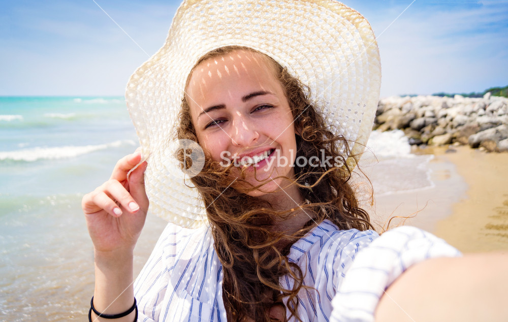 Beautiful young woman on beach wearing striped blue-and-white shirt and hat, smiling, taking selfie. Enjoying time at seaside.