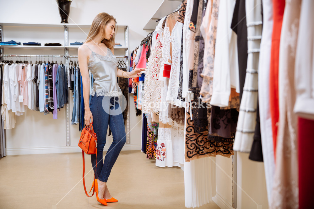Beautiful young woman standing and choosing clothes in clothing store