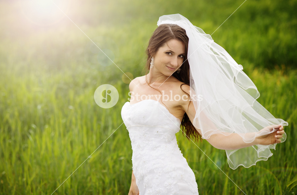 Bride in white wedding dress at the meadow