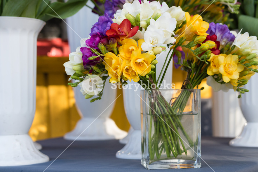 Bright colored flowers in a transparent vase with water