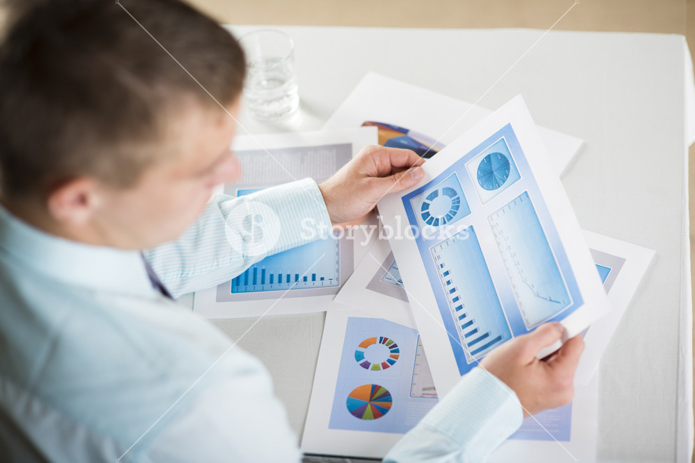 Business people reading graphs and charts