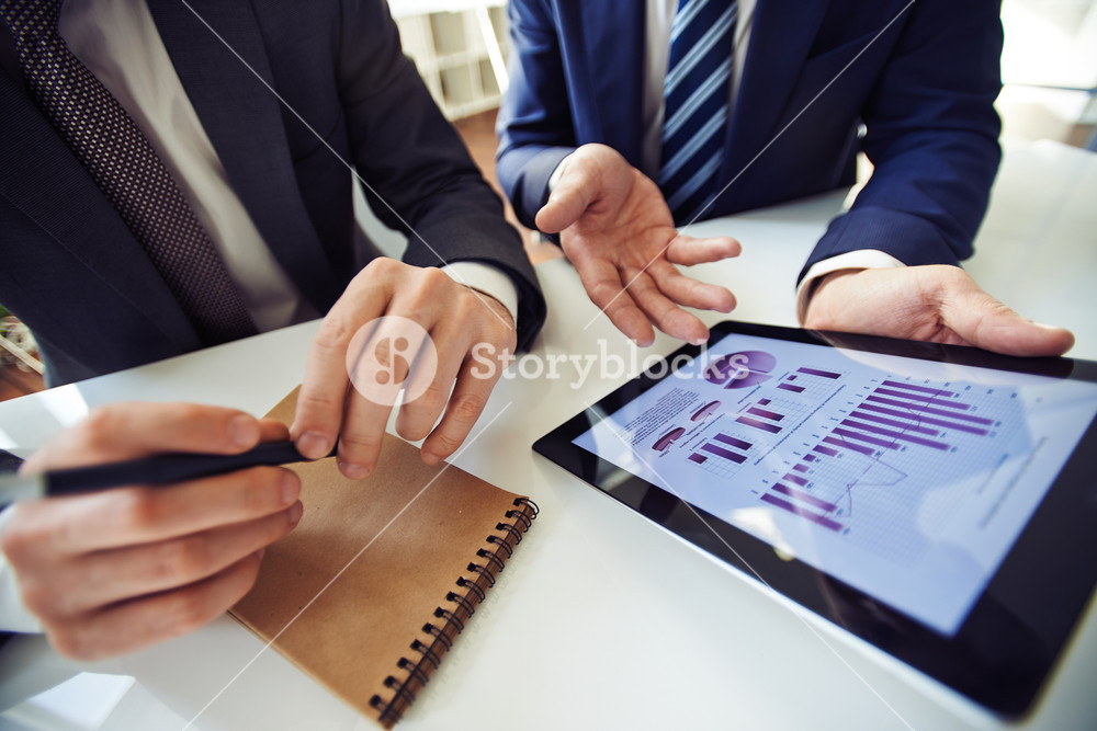 Businessmen discussing electronic data in touchpad